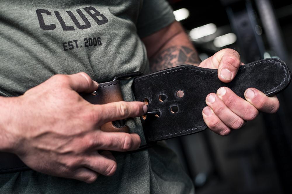 man tightening weightlifting belt