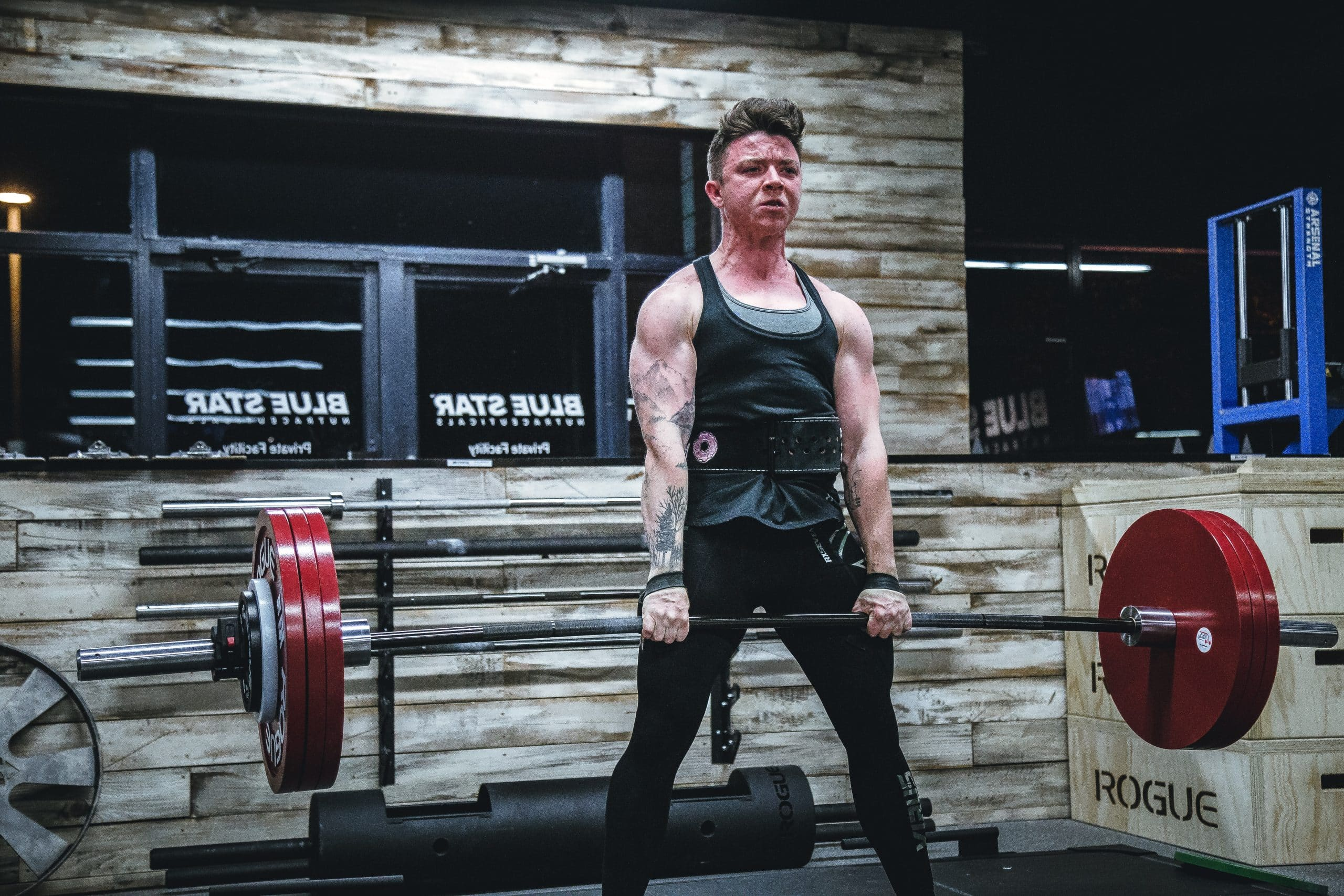 Woman performing deadlifts while breathing out using a valeo lifting belt